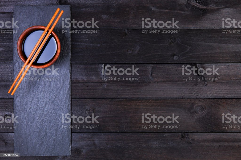 Background for sushi. Soy sauce, chopsticks on black table. Top view with copy space stock photo