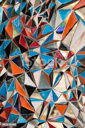 Background formed by colored glass triangles and mirrors.