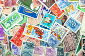 Background from a variety of multi-colored postage stamps from different countries and years