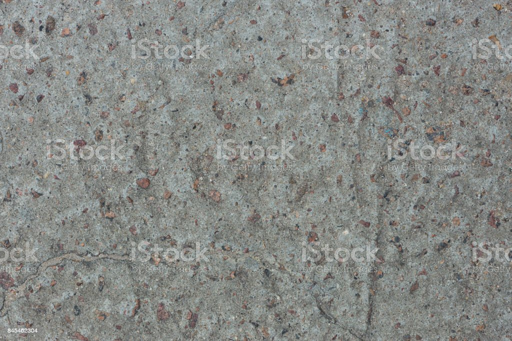Background from concrete with impregnations from red granite gravel with an uneven surface стоковое фото