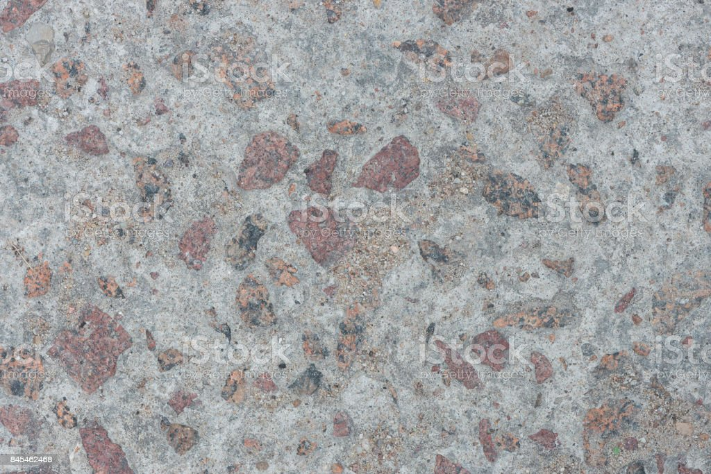 Background from concrete with large impregnations of red granite with an uneven surface стоковое фото