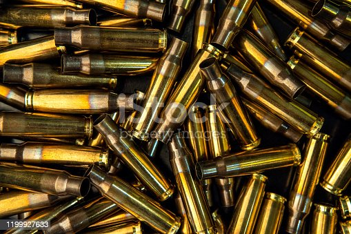 istock Background from empty cartridges for rifles and carbines. Shiny brass shells scattered on the surface. 1199927633