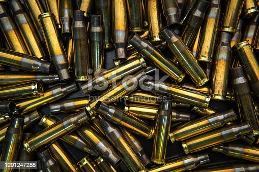 istock Background from empty cartridges for rifles and carbines. Shiny brass shells scattered on the surface. 1201247288