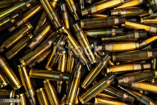 istock Background from empty cartridges for rifles and carbines. Shiny brass shells scattered on the surface. 1203626361
