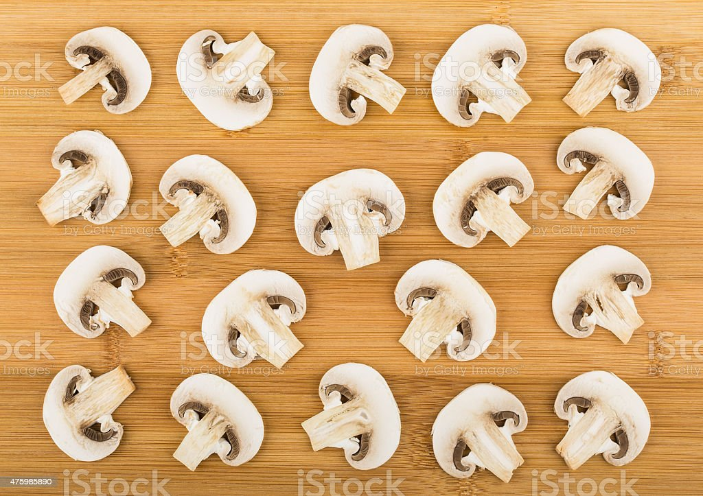 Background from slices of raw champignons on board stock photo