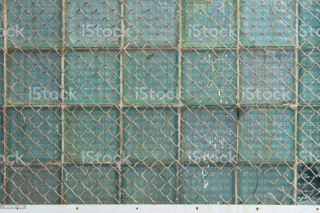 Background from the metal gauze of the chain-link and glass blocks стоковое фото