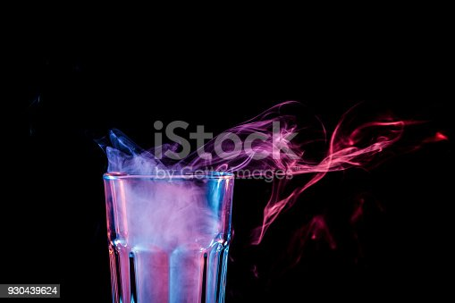 Close up of a new glass with soft multi-colored pink smoke from vape on a black isolated background