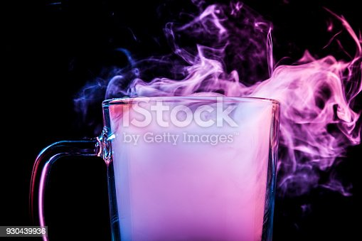 Close up of a  transparent  glass for beer filled with a cloud from a purple vape smokes and stands on a black isolated background