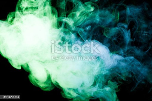 Colorful yellow  and green a smoke  on a black isolated background. Background from the smoke of vape