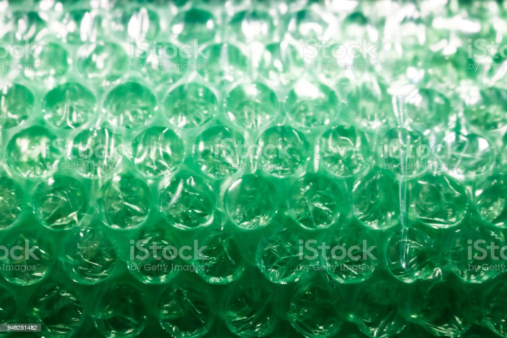 Background - green bubble wrap - selective focus - lighter at the top and darker at the bottom stock photo