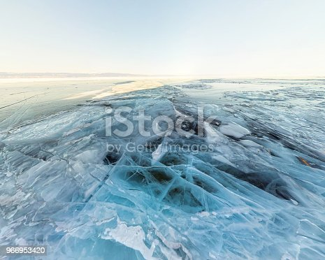 Background ice blue crystal clear lake covered with cracks.