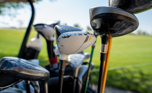 Background image of multiple golf sticks on the behind of a golf cart.