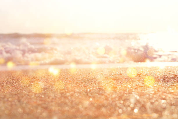 background image of sandy beach and ocean waves with bright bokeh lights – zdjęcie