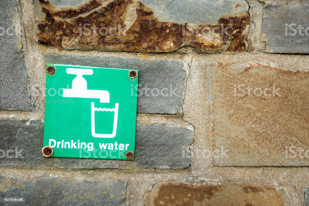 Background image Old stone wall with Drinking Water sign stock photo