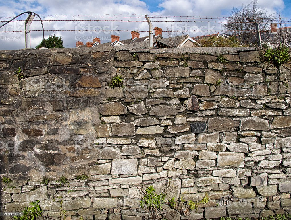 Background image Old stone wall with wire on top stock photo
