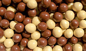 Background made of chocolate hazelnuts covered with milk chocolate and white chocolate. Choco hazelnuts dragee backdrop
