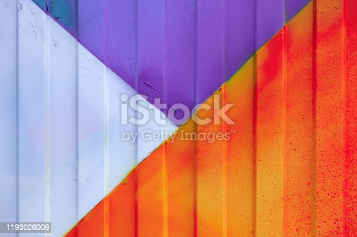 Background made of metal profile painted in purple, orange, red and white on the fence or container. Construction in the city.