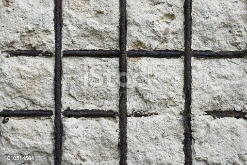 Concrete wall with rusty reinforcement rods background. Texture of old gray concrete wall for background