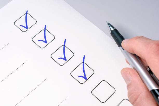 Background of a checklist with checked tasks and a pen-holding hand checklist chores stock pictures, royalty-free photos & images