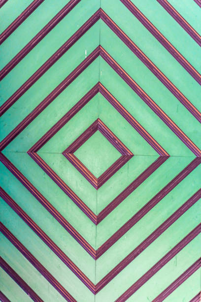 background of a handmade wooden door with a diamond pattern in green and brown stock photo