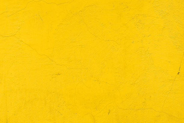 A background of a plain yellow wall Cracked yellow painted wall yellow stock pictures, royalty-free photos & images
