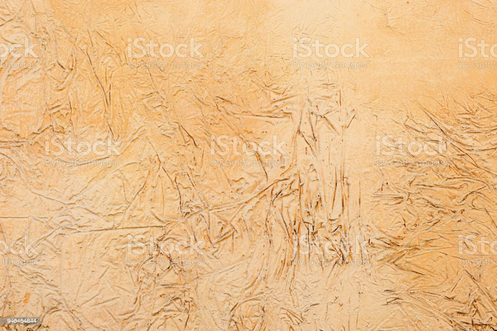 Background of a yellow stucco coated and painted exterior, rough cast of cement and concrete wall texture stock photo