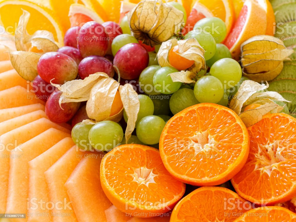 Background of arranged freshly cut tropical and citrus fruit. Closeup.