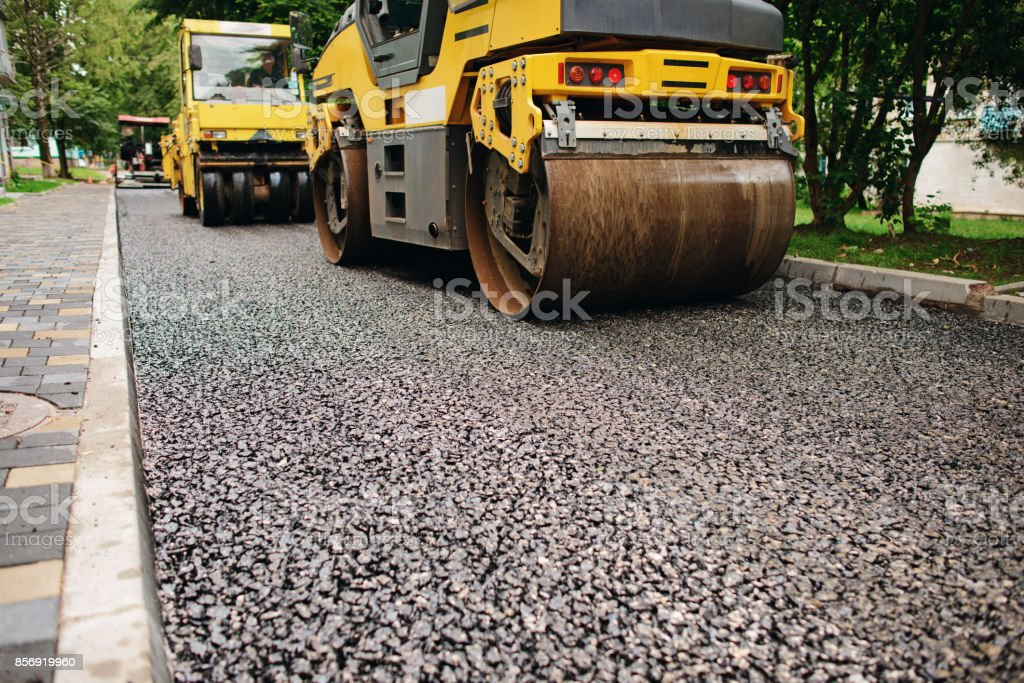 Background of asphalt roller that stack and press hot asphalt. Road repair machine stock photo