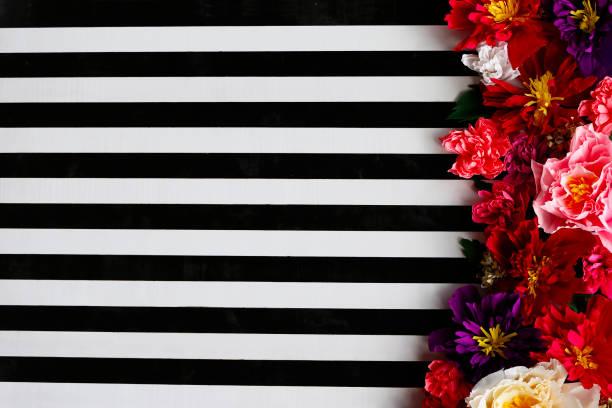 hintergrund aus schwarzen und weißen streifen und leuchtend großen blüten - blumenstreifen stock-fotos und bilder