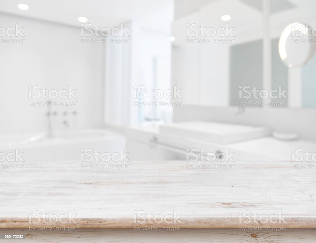 Background of blurred bathroom interior with wooden table in front stock photo