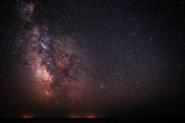 hintergrund hell und nacht sternenklaren himmel mit der milchstraße auf drauf und licht über dem wasser - sternhaufen stock-fotos und bilder