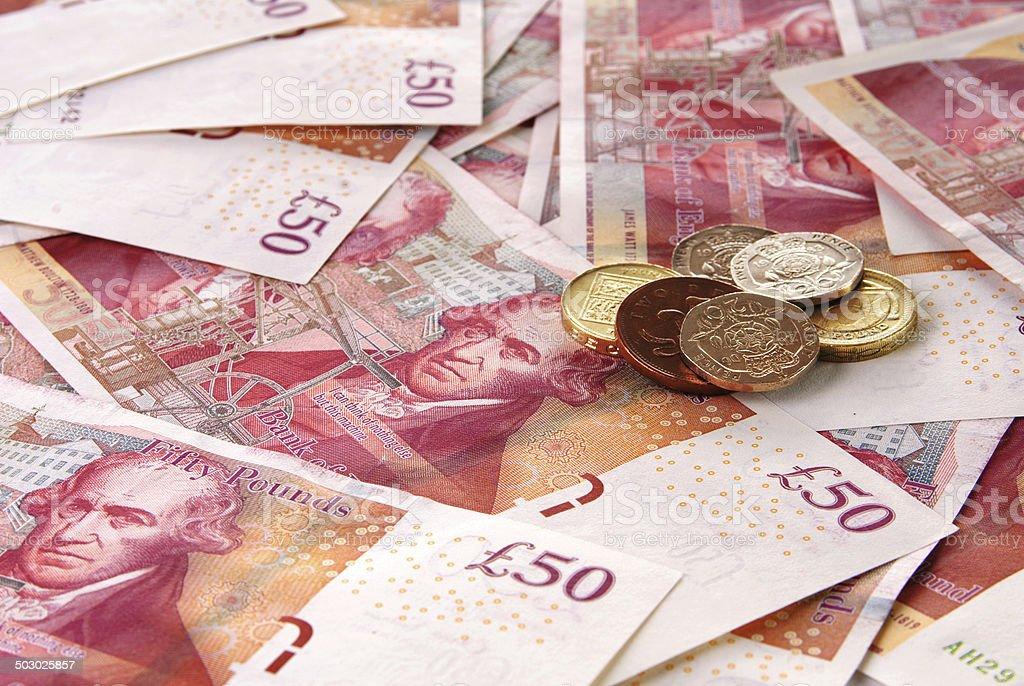 Fond de billets de 50 livres sterling britanniques et une pile de pièces de monnaie - Photo