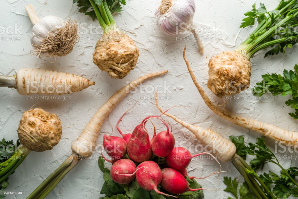 Background of celery roots, parsley, radishes with leaves and garlic on white table stock photo