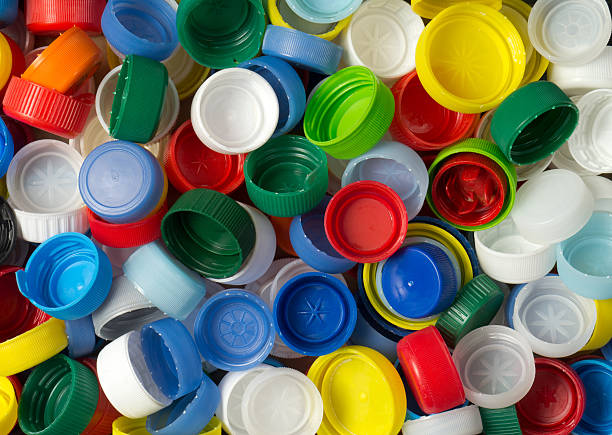 background of close-up rainbow colored plastic screw caps - plastic cap stock pictures, royalty-free photos & images