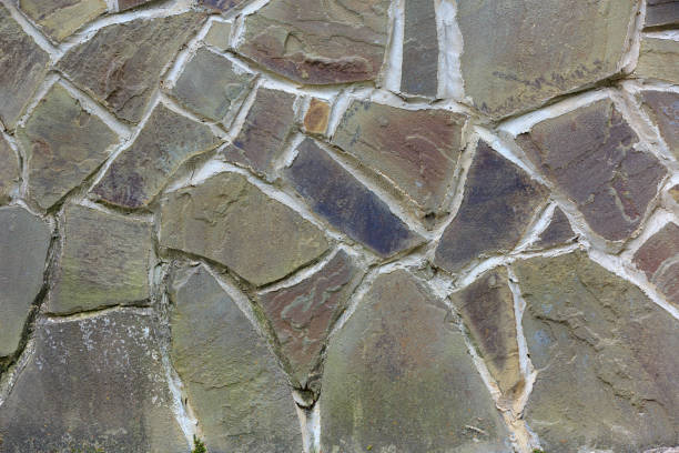 Background of colorful old limestone with rough wide cement joints stock photo