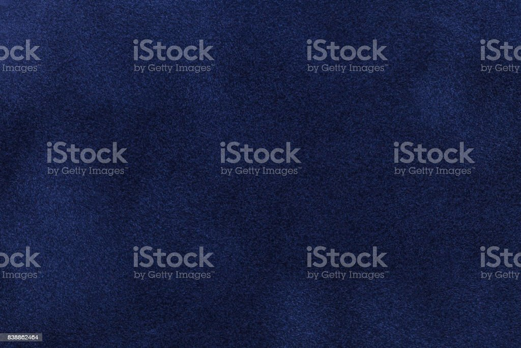 Background of dark blue suede fabric closeup. Velvet matt texture of navy blue nubuck textile
