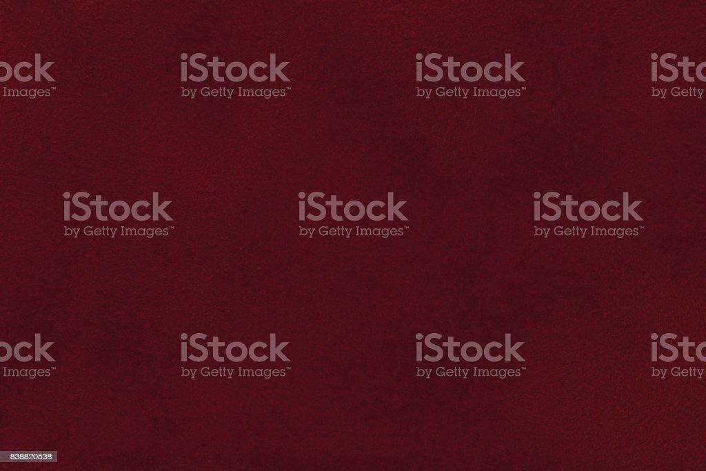 Background of dark red suede fabric closeup. Velvet matt texture of wine nubuck textile