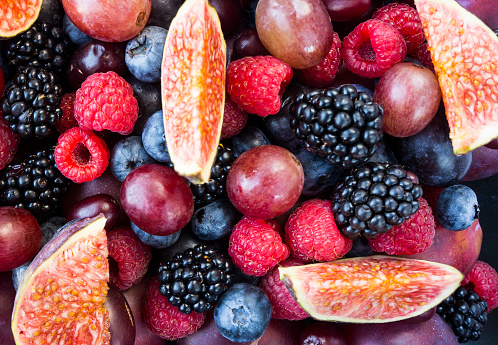 istock Background of fresh fruits and berries. Ripe blackberries, blueberries, plums, pink grapes, raspberries and figs. Mix berries and fruits. Top view. Background berries and fruits. Various fresh summer fruits. Black-blue and red food. 1139090306