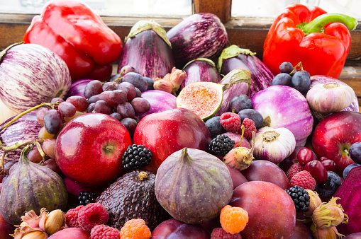 istock Background of fresh vegetables and fruits. Purple eggplant, plums, figs, apples, raspberries, avocado, grape, hazelnut, sweet pepper, tomato and garlic. Purple and red food. Different vegetables on the table. 1191398097