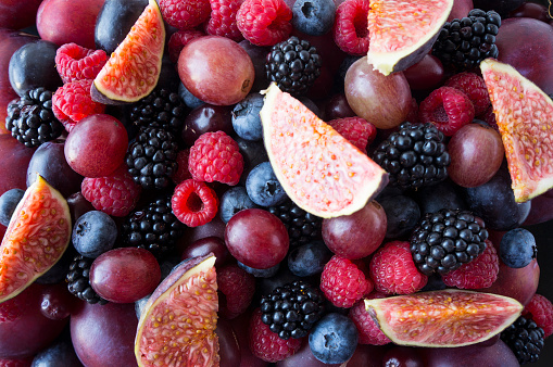 istock Background of fresh vegetables and fruits. Ripe blackberries, blueberries, plums, pink grapes, raspberries and figs. Mix berries and fruits. Top view. Background berries and fruits. Various fresh summer fruits. Black-blue and red food. 1130725758