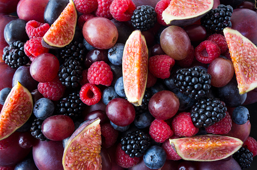 istock Background of fresh vegetables and fruits. Ripe blackberries, blueberries, plums, pink grapes, raspberries and figs. Mix berries and fruits. Top view. Background berries and fruits. Various fresh summer fruits. Black-blue and red food. 1134304118