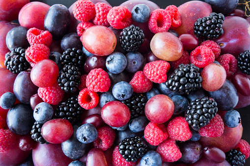 istock Background of fresh vegetables and fruits. Ripe blackberries, blueberries, plums, pink grapes, raspberries. Mix berries and fruits. Top view. Background berries and fruits. Various fresh summer fruits. Black-blue and red food. 1200941525