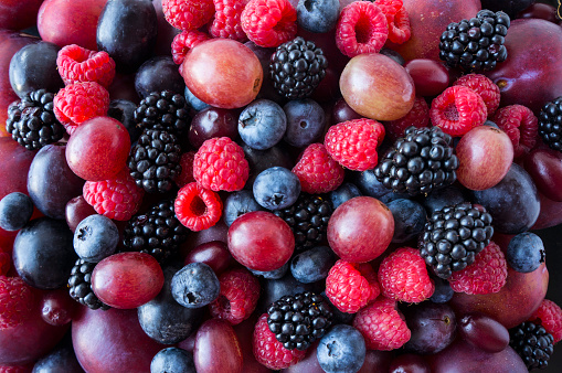 istock Background of fresh vegetables and fruits. Ripe blackberries, blueberries, plums, pink grapes, raspberries. Mix berries and fruits. Top view. Background berries and fruits. Various fresh summer fruits. Black-blue and red food. 1209030808