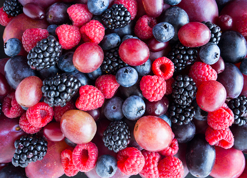 istock Background of fresh vegetables and fruits. Ripe blackberries, blueberries, plums, pink grapes, raspberries. Mix berries and fruits. Top view. Background berries and fruits. Various fresh summer fruits. Black-blue and red food. 1250469732