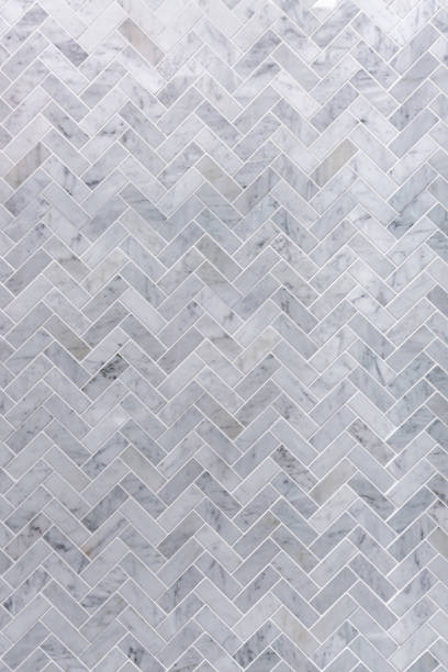 background of grey and white marble tile in herringbone pattern - tile stock photos and pictures