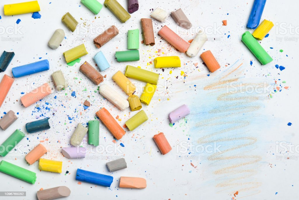 Background of many multicolored pastel crayons on a white background,...