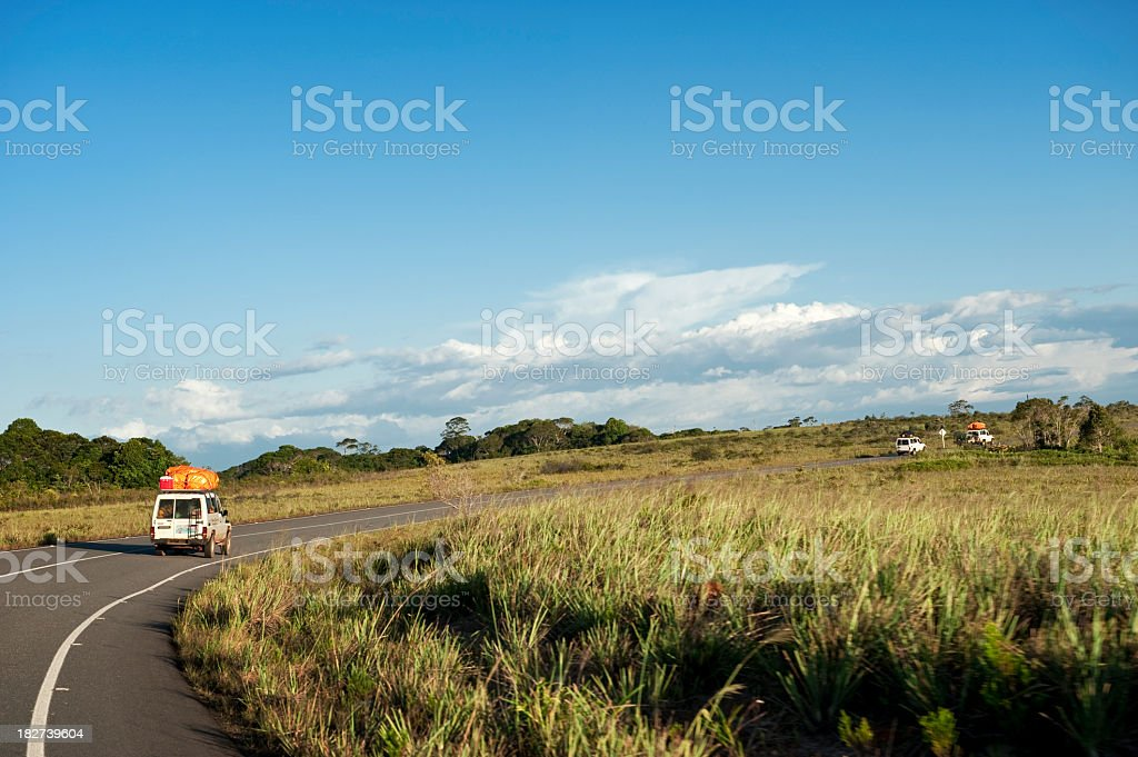 Background of off-road vehicles on green landscape with road royalty-free stock photo