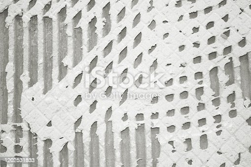 1138442636 istock photo Background of old tile adhesive on wall, pattern of notched trowel. 1202531833