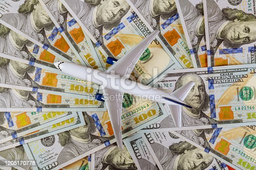 istock Background of one hundred dollar bills with model plane, on flat lay design to travel concept 1205170778