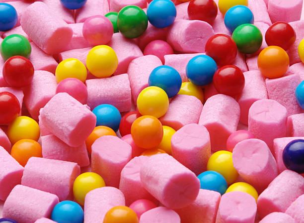 background of pink cylinder shaped gum and colorful gumballs - kauwgom stockfoto's en -beelden